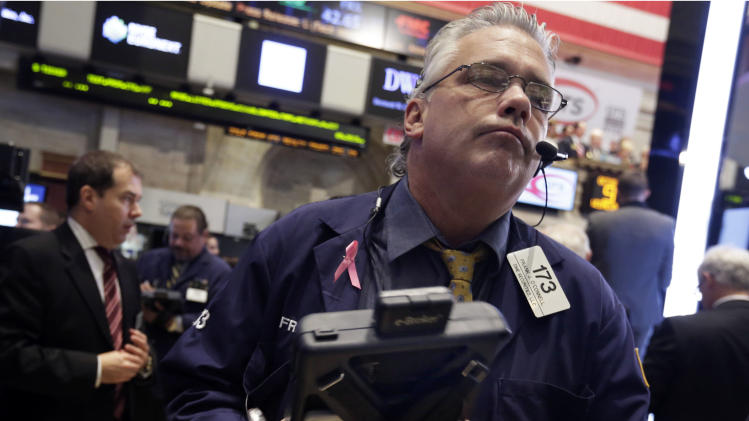In this Wednesday, Oct. 9, 2013 photo, trader Frank O'Connell, right, works, on the floor of the New York Stock Exchange. U.S. futures are down sharply, Monday, Oct. 14, 2013, as the nation heads into the third week of a partial government shutdown. (AP Photo/Richard Drew)