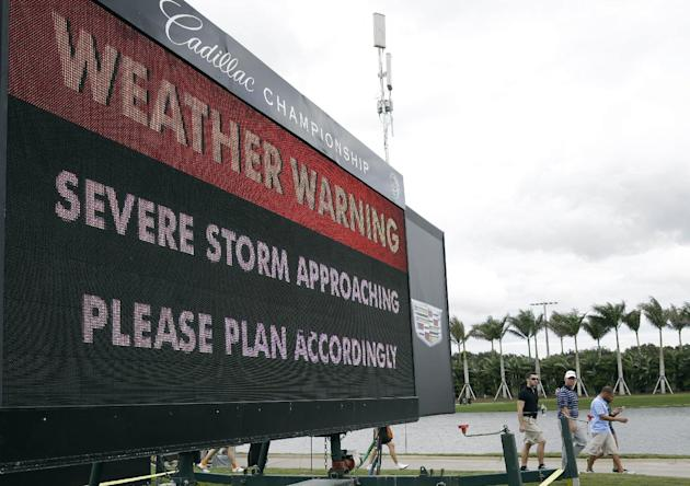 Spectators leave the golf course after play was suspended due to approaching inclement weather during the first round of the Cadillac Championship golf tournament, Thursday, March 6, 2014, in Doral, F