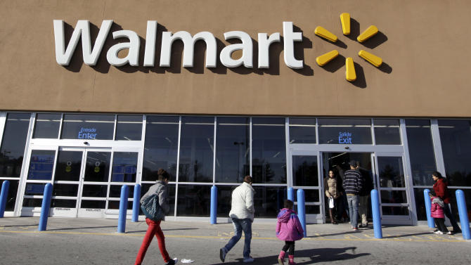 FILE - In this Feb. 20, 2012, file photo, customers walk into and out of a Wal-Mart store in Methuen, Mass.  Wal-Mart Stores Inc. reported a 5.7 percent increase in second-quarter net income and raised its outlook for the full year as the world's largest retailer continues to woo back frugal shoppers by re-emphasizing that it has the lowest prices on everything from clothes to electronics. But Wal-Mart said Thursday, Aug. 16, 2012,  that its total revenue came in short of Wall Street estimates, and the discounter announced that it would delay store expansion plans in Mexico, its largest international division, as it deals with bribery charges there. Investors, who had sent the stock up 25 percent since mid-May, pushed shares down more than 3 percent on the news.  (AP Photo/Elise Amendola, File)