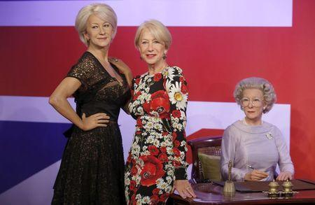 British actor Helen Mirren poses with waxwork models of herself at Madame Tussauds in London