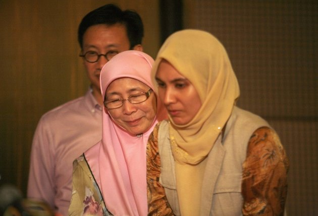 Wan Azizah Wan Ismail, wife of Malaysia's opposition leader Anwar Ibrahim, leaves with their daughter Nurul Izzah (R) after a news conference in Kuala Lumpur early May 6, 2013. Malaysia's ruling National Front coalition won a simple majority of 112 seats in the 222-seat national parliament in Sunday's election, the country's Election Commission said, signalling it would extend its 56-year rule in the Southeast Asian nation. REUTERS/Samsul Said (MALAYSIA - Tags: POLITICS ELECTIONS)