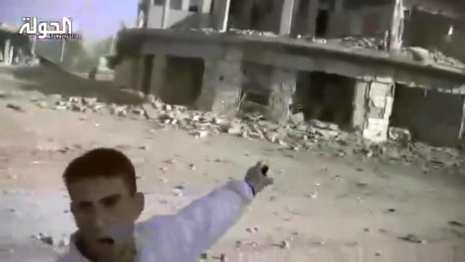 This image taken from video obtained from Shaam News Network, which has been authenticated based on its contents and other AP reporting, shows a man gesturing toward buildings destroyed in heavy bombing from military warplanes in Houla, Syria, Tuesday, Nov. 6, 2012. The Britain-based Syrian Observatory for Human Rights said air raids on Houla, a group of villages in central province of Homs, killed several people.(AP Photo/Shaam News Network via AP video)