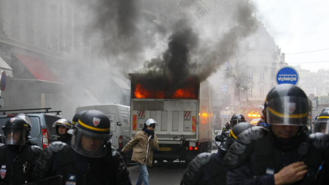 Riot police officers move back from a burning truck during clashes with youths in Lyon, central France, Wednesday Oct. 20, 2010. French authorities forced strike-shuttered fuel depots to reopen to ensure gasoline supplies, and the interior minister threatened Wednesday to send in paramilitary police to stop rioting on the fringes of protests against raising the retirement age to 62. Months of largely peaceful demonstrations against the pension reform have taken a violent turn in recent days. (AP Photo/Michel Spingler)