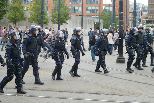 Riot police patrol Manchester city centre after trouble  on Market street  in Manchester city centre, England,  Tuesday Aug. 9, 2011.  Britain began flooding London's streets with 16,000 police office
