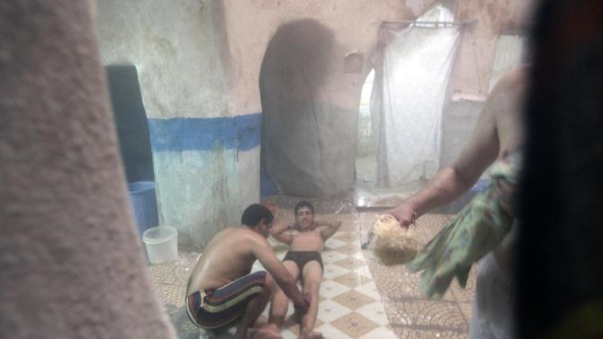 A worker scrubs a man as he takes a bath at a hammam in Najaf