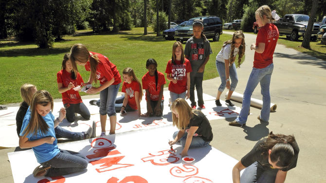 Kountze High School cheerleaders and other children work on a large sign Wednesday, Sept. 19, 2012 in Kountze, Texas.  The small Hardin County community is rallying behind the high school's cheerleaders after the squad members were told they could not use scripture verses on their signs at the football games. (AP Photo/The Beaumont Enterprise, Dave Ryan)