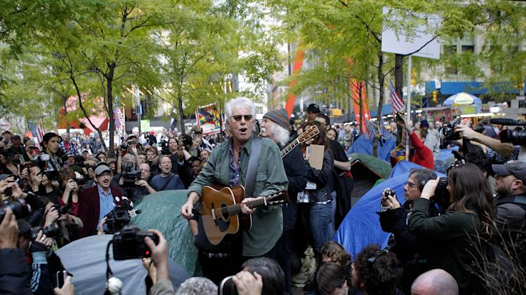 "FILE - In this Nov. 8, 2011 file photo, singers Graham Nash, center left, and David Crosby, center right, perform a free acoustic concert of protest songs at Occupy Wall Street's Zuccotti Park encampment in New York. Music is woven into the fabric of Occupy Wall Street, much like when civil rights protesters sang ""We Shall Overcome"" or 1960s demonstrators heard ""Blowin' in the Wind"" or ""Give Peace a Chance."" Crosby and Nash's manager sent an email to Occupy Wall Street's website asking if the musicians could perform.  (AP Photo/Kathy Willens, file)"