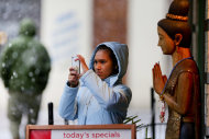While standing in front of Thai Continental Cuisine restaurant, Kratai Fisher takes a picture of heavy snow falling in downtown Roanoke, Virginia on Thursday afternoon Jan. 17, 2013. Virginia is bracing for the first significant snowstorm of the winter season. (AP Photo/The Roanoke Times, Kyle Green) LOCAL TV OUT; SALEM TIMES REGISTER OUT; FINCASTLE HERALD OUT; CHRISTIANBURG NEWS MESSENGER OUT; RADFORD NEWS JOURNAL OUT; ROANOKE STAR SENTINEL OUT MBI