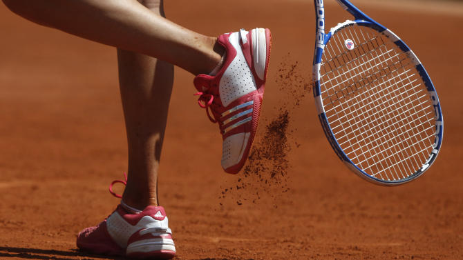 Russia's Anastasia Pavlyuchenko uses her reacket to remove clay from her shoe as she plays compatriot Vera Zveranova during their fourth round match of the French Open tennis tournament, at  the Roland Garros stadium in Paris, Sunday, May 29, 2011. Pavlyuchenko  won 7-6, 2-6, 6-2. (AP Photo/Michel Spingler)
