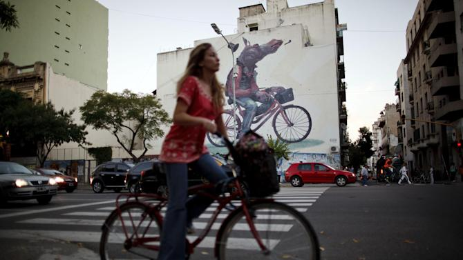 In this March 27, 2013 photo, a woman commutes on a bicycle past a mural of a horse riding a bike by Spain's artist Aryz in Buenos Aires, Argentina. International artists come to Buenos Aires to spray-paint graffiti as well as other styles and methods of street art because local authorities have shown themselves receptive to the creations, said Matt Fox-Tucker, an Englishman who created a website focusing on urban murals around the city. (AP Photo/Natacha Pisarenko)