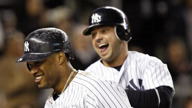 New York Yankees' Nick Swisher, right, celebrates with teammate Robinson Cano after scoring on Cano's fifth-inning two-run home run during their baseball game against the Tampa Bay Rays at Yankee Stadium in New York, Thursday, May 10, 2012. (AP Photo/Kathy Willens)