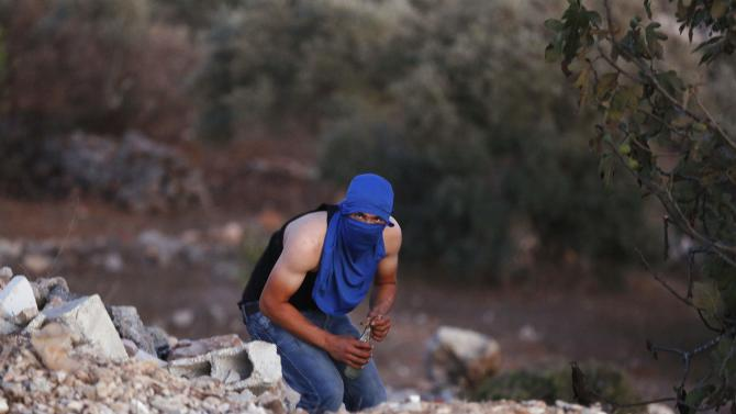 A Palestinian protester prepares to hurl a Molotov cocktail towards Israeli troops during clashes at a protest against the Jewish settlement of Ofra, in West Bank