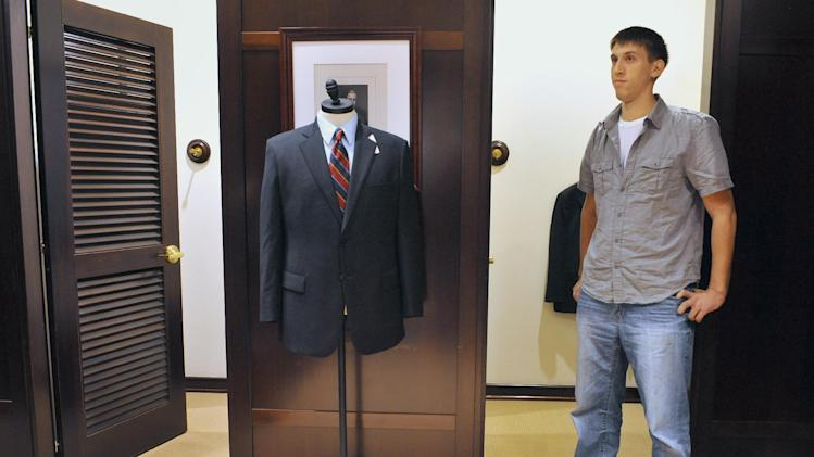 In this Thursday, Sept. 20, 2012 photo, Marine Corps veteran Tim Hudak of Alexandria, Va. waits to be fitted for a suit provided by Brooks Brothers in West Hartford, Conn. Hudak is participating in the University of Connecticut's Entrepreneurship Bootcamp for Veterans with Disabilities. More than 200,000 people are discharged from the U.S. military each year, and advocates say they often possess qualities that make good entrepreneurs: resourcefulness, a taste for risk-taking and a can-do attitude. Nonprofit groups, state governments and U.S. agencies are all providing business training aimed at giving them new purpose and easing their transition to civilian life. (AP Photo/Jessica Hill)
