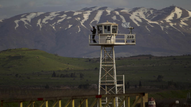 A U.N. peacekeeper from the UNDOF force stands guard on a watch tower at the Quneitra Crossing between Syria and the Israeli-controlled Golan Heights, Friday, March 8, 2013. Syrian rebels who seized 21 Filipino U.N. peacekeepers in the Golan Heights want the Red Cross to escort them out of the area because of fighting with Syrian government forces, the Philippine military said Friday. The 21 peacekeepers were seized Wednesday near the Syrian village of Jamlah, just a mile from the Israeli-controlled Golan Heights in an area where the U.N. force had patrolled a cease-fire line between Israel and Syria without incident for nearly four decades. (AP Photo/Ariel Schalit)