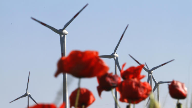 "FILE - In this June 3, 2011 file photo windmills are pictured behind poppy blossoms in Nauen-Berge near Berlin, Germany. The crisis in Ukraine is underlining the urgency of Germany's biggest political challenge as Chancellor Angela Merkel's new government marks 100 days in office Wednesday, March 26, 2014, getting the country's mammoth transition from nuclear to renewable energy sources on track. The transition started in earnest when Merkel, after Japan's 2011 Fukushima nuclear disaster, abruptly accelerated Germany's exit from nuclear power. Since then, the ""Energiewende"" _ roughly, ""energy turnaround"" _ has created increasing headaches. (AP Photo/Ferdinand Ostrop, File)"