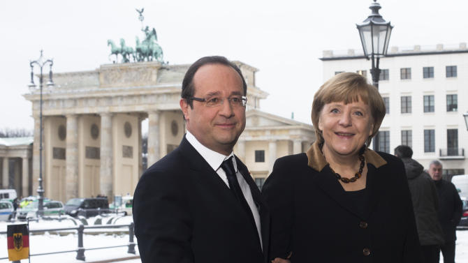 French President Francois Hollande, left, welcomes German Chancellor Angela Merkel in front of the Brandenburg Gate near the France embassy in Berlin, Tuesday, Jan. 22, 2013. They meet as part of events marking the 50th anniversary of the signing of the Elysee Treaty, a landmark accord cementing reconciliation between the two European powers. (AP Photo/Markus Schreiber)