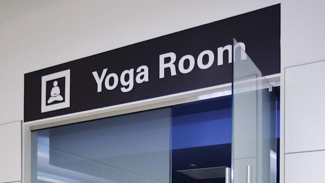 In this Friday, Jan. 27, 2012 photo, traveler Maria Poole leaves San Francisco International Airport's new Yoga Room, in San Francisco. The quiet, dimly lit studio officially opened last week in a former storage room just past the security checkpoint at SFO's Terminal 2. Airport officials believe the 150-square-foot room with mirrored walls is the world's first airport yoga studio, said spokesman Mike McCarron. (AP Photo/Paul Sakuma)