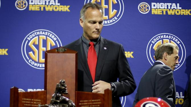 Georgia head coach Mark Richt, left, lingers after posing with Alabama head coach Nick Saban, right, and the Southeastern Conference championship trophy, before he takes his turn at a press conference ahead of Saturday's SEC championship college football game, Friday, Nov. 30, 2012, in Atlanta. (AP Photo/David Goldman)