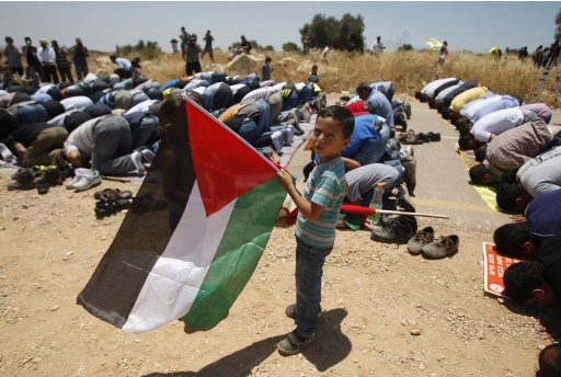 A Palestinian boy holds a flag as he stands near men taking part in Friday prayers in the West Bank village of Bilin, near Ramallah