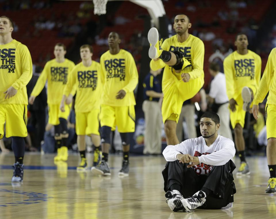 Louisville guard Peyton Siva sits on the floor as Michigan players warm up during the first half of the NCAA Final Four tournament college basketball championship game Monday, April 8, 2013, in Atlanta. (AP Photo/Charlie Neibergall)