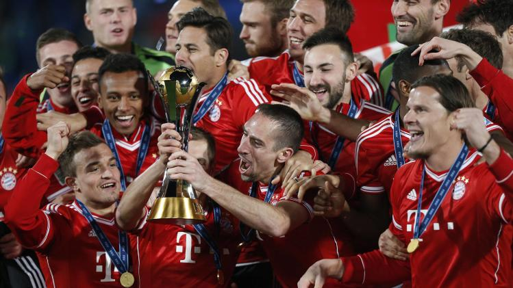 Germany's Bayern Munich Franck Ribery and Philipp Lahm hold the trophy as they celebrate with their team mates after winning their 2013 FIFA Club World Cup final soccer match against Morocco's Raja Casablanca at Marrakech stadium