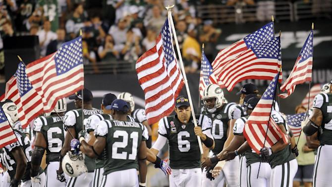 New York Jets quarterback Mark Sanchez (6) runs onto the field carrying an American flag before an NFL football game between the Dallas Cowboys and New York Jets on Sunday, Sept. 11, 2011,  in East Rutherford, N.J. (AP Photo/Henny Ray Abrams)