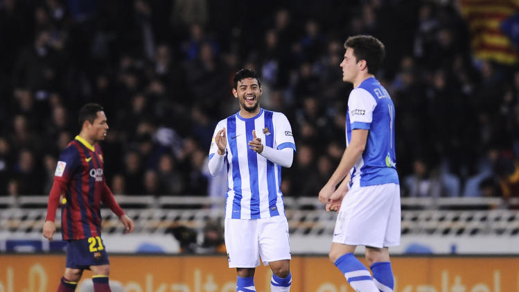 Real Sociedad's Carlos Vela of Mexico, center, applauds after his team scored while FC Barcelona's Adriano Correia of Brazil, left, looks at, during the Spanish League soccer match, at Anoeta stadium in San Sebastian, Spain, Saturday, Feb. 22, 2014. (AP Photo/Alvaro Barrientos)