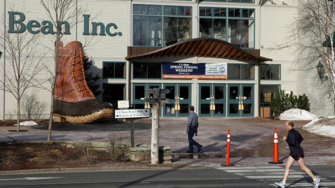FILE - In this March 8, 2012 file photo, a jogger passes by the entrance to the L.L. Bean retail store in Freeport, Maine. L.L. Bean says sales grew 5.5 percent over the past year despite a mild winter weather that hurt sales of skis, coats and other outdoor gear for which the company is known. (AP Photo/Robert F. Bukaty, File)