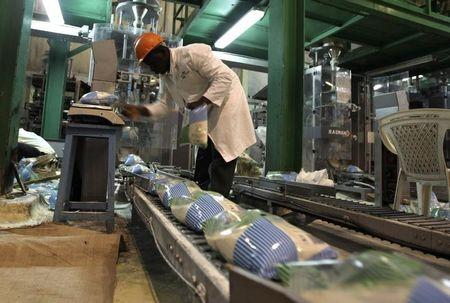 A worker arranges packets of sugar on a conveyor belt at the Mumias sugar factory in western Kenya