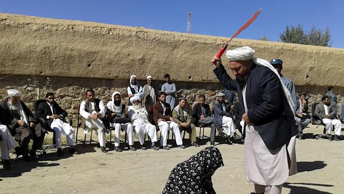 Afghan judge hits a woman with a whip in front of a crowd in Ghor province