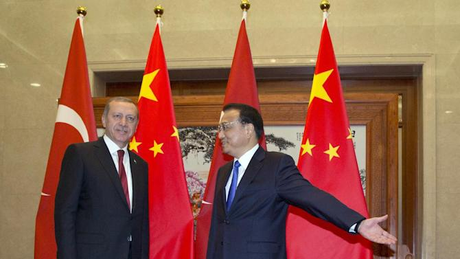 Turkey's President Recep Tayyip Erdogan, left, is shown the way by Chinese Premier Li Keqiang at the Great Hall of the People in Beijing, Wednesday, July 29, 2015. Erdogan met with top Chinese officials Wednesday amid tensions over China's treatment of its Uighur minority and sensitive negotiations surrounding the possible purchase of a Chinese missile system. (AP Photo/Ng Han Guan, Pool)
