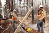 A crew from PG&E works Wednesday, Aug. 22, 2012, to restore power to a rural subdivision overrun by fire by the Ponderosa Fire outside Manton, Calif. The fire continued to grow Thursday, burning through 44 square miles after burning 84 homes and other buildings in an area about 30 miles southwest of Redding, Calif. (AP Photo/Jeff Barnard)