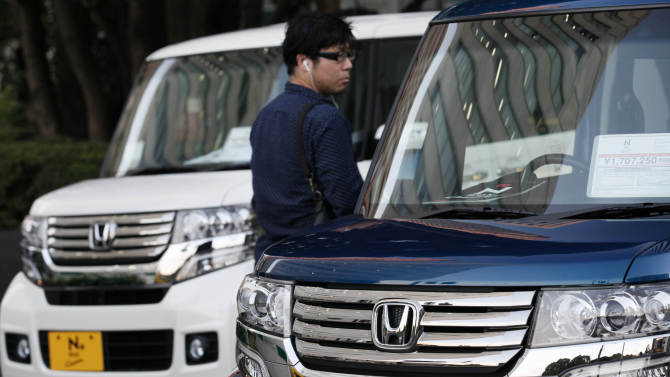 FILE - In this Oct. 29, 2012 file photo, a man inspects Honda vehicles displayed in front of Honda Motor Co. headquarters in Tokyo. Honda's quarterly profit surged nearly 63 percent as production recovered after disruptions from natural disasters. The Japanese automaker reported a 77.4 billion yen (US$850 million) profit for the October-December period Thursday, as sales jumped nearly 25 percent to 2.4 trillion yen (US$26 billion). (AP Photo/Koji Sasahara, File)