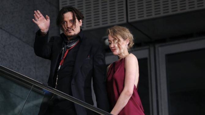 "Actor Johnny Depp waves to fans next to Amber Heard as they leave the Japan premiere of ""Mortdecai"" in Tokyo"