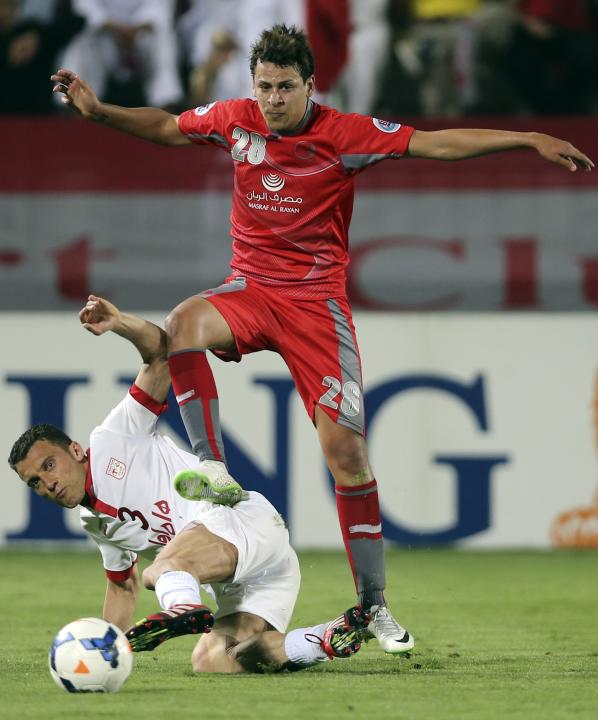Youssef Msakn of Qatar's Lekhwiya fights for the ball with Habib Gordani of Iran's Tractor Sazi FC during their AFC Champions League soccer match in Doha