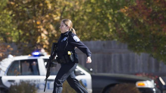 A police officer responds to a call of a shooting at the Azana Spa in Brookfield, Wis. Sunday, Oct. 21, 2012.  Multiple people were wounded when someone opened fire at the spa near the Brookfield Square Mall.   (AP Photo/Tom Lynn)
