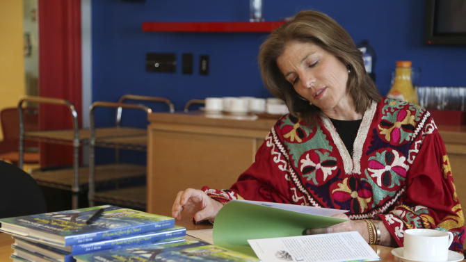 """In this Tuesday, March 26, 2013 photo, Caroline Kennedy flips through her new book """"Poems to Learn by Heart"""" during an interview with The Associated Press in New York. Kennedy's 10th and latest book extols the value of learning poems by heart. (AP Photo/Mary Altaffer)"""
