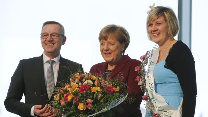 German Chancellor Merkel poses with Flower Fairy 2015/2016 Berchtenbreiter and the head of Central Gardening Association Mertz at the Chancellery in Berlin