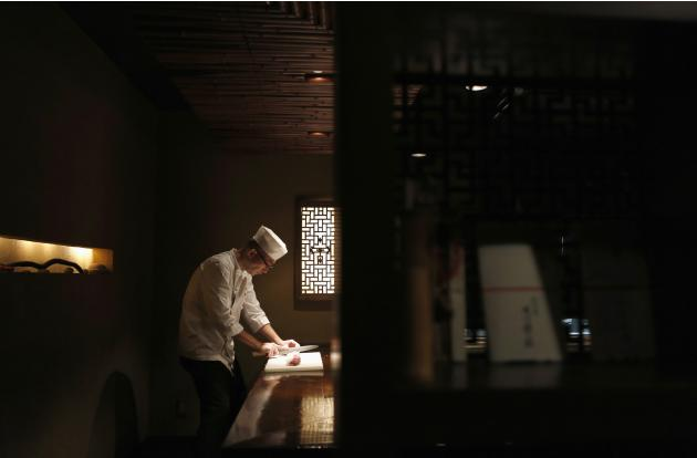 A chef slices a portion of greater amberjack while preparing sashimi at the Akasaka Umaya Japanese-style restaurant in Tokyo
