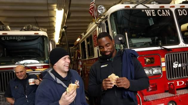 NFL star Justin Tuck surprises members of the FDNY at a fire house with free subs to kick off Subway's Customer Appreciation Month on December 3, 2013 in New York -- AP