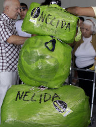 Wrapped packages with the name Nelida written on them are piled up on a dolly as their their owner, Cuban-American Nelida Diaz, stands behind right as she arrives to the Jose Marti International Airport from a U.S. bound flight in Havana, Cuba, Monday, Sept. 3, 2012. A steep hike in customs duties has taken effect Monday in Cuba, catching some air travelers unaware. Diaz says she was shocked when officials charged her $588 at customs. (AP Photo/Franklin Reyes)