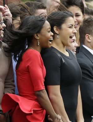 Members of the 2012 Women's Olympic Gymnastics team, Gabby Douglas, left, McKayla Maroney, right, react to the wind gust caused by the Marine One helicopter, with President Barack Obama aboard, as they watch the departure from the South Lawn of the White House in Washington, Thursday, Nov. 15, 2012. Obama had met privately with the team earlier in the Oval Office. (AP Photo/Pablo Martinez Monsivais)