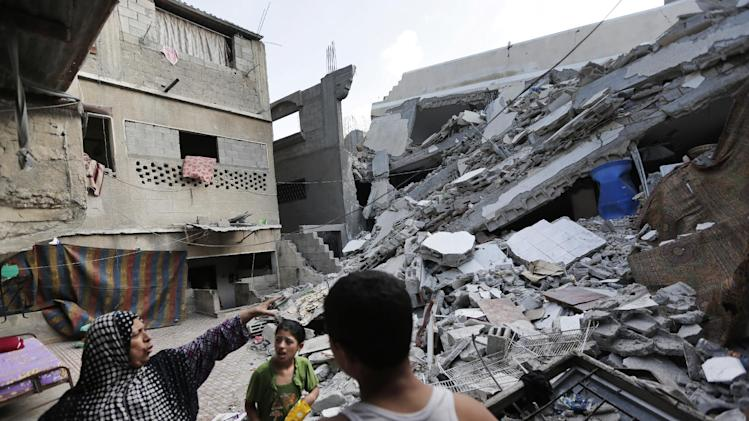 Palestinian Heygar Jendiyah, left, points to where the family house kitchen once stood, partially destroyed by an Israeli strike earlier during the war, as her children Ranin, 10, center, and Helmi, right, listen, in the Sabra neighborhood of Gaza City, northern Gaza Strip, Thursday, July 31, 2014. The building houses 21 members of the extended family, and now with several rooms destroyed, they try to go about their lives, without electricity and without running water for many hours a day. (AP Photo/Lefteris Pitarakis)