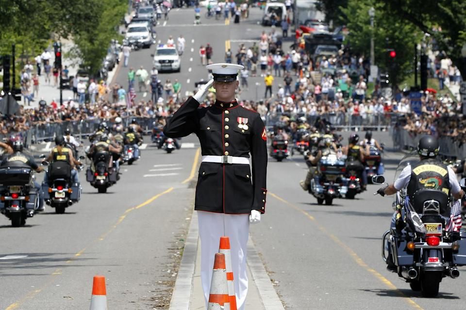 A Marine salutes as motorcycles drive past during the annual Rolling Thunder parade ahead of Memorial Day in Washington, Sunday, May 27, 2012. (AP Photo/Charles Dharapak)