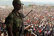 A soldier from the M23 rebel group looks on as thousands of Congolese people listen during an M23 rally, in Goma, eastern Congo, Wednesday, Nov. 21, 2012. Thousands of Congolese soldiers and policemen defected to the M23 rebels Wednesday, as rebel leaders vowed to take control of all Congo, including the capital Kinshasa. The rebels organized a rally at Goma&#39;s Stadium of Volcanoes after seizing control of the strategic city in eastern Congo Tuesday. (AP Photo/Marc Hofer)