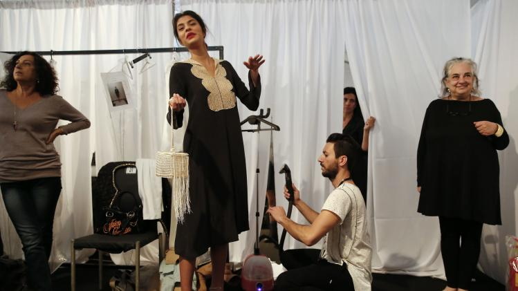 A model reacts as her outfit by Israeli designer Tamara Salem is steamed backstage during Tel Aviv Fashion Week