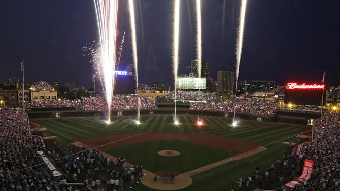 Fans watch a Fourth of July fireworks display after the Chicago Cubs defeated the Miami Marlins 7-2 in a baseball game Saturday, July 4, 2015, in Chicago. (AP Photo/Nam Y. Huh)