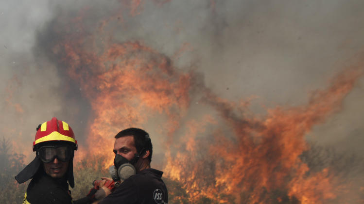 Firefighters work to control a fire near the town of Palea Fokaia, south of Athens, Saturday, June 16, 2012. The fire started in the early Saturday afternoon on dried grass, apparently as the result of an accident and has been spreading fast, threatening to engulf isolated houses on the outskirts of the towns of Keratea and Palea Fokaia. (AP Photo/Kostas Tsironis)