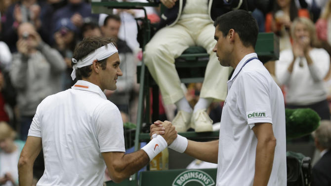Roger Federer of Switzerland, left, shakes hands with Victor Hanescu of Romania after beating him in their Men's first round singles match at the All England Lawn Tennis Championships in Wimbledon, London, Monday, June 24, 2013. (AP Photo/Anja Niedringhaus)