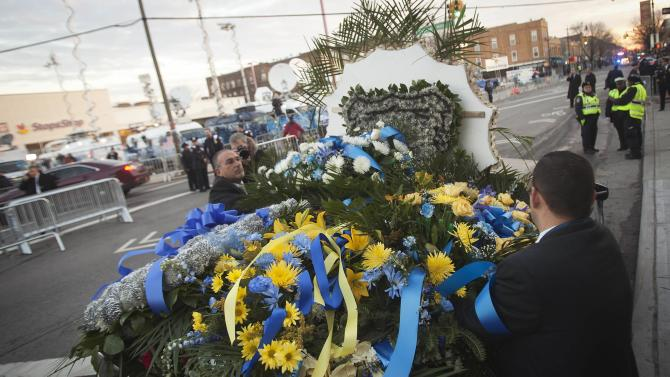 Funeral workers put flowers in a car before NYPD officer Rafael Ramos funeral at Christ Tabernacle Church to it's final resting place in the Queens borough of New York